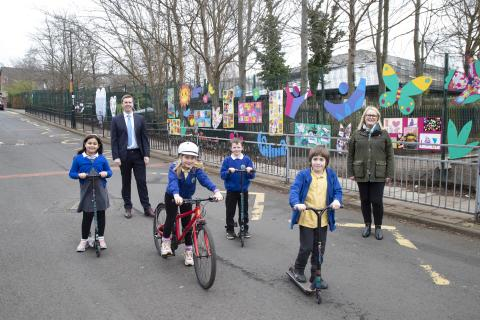 Image showing four primary school children in uniform, three on scooters, one on a bike, outside a school with two adults standing alongside.
