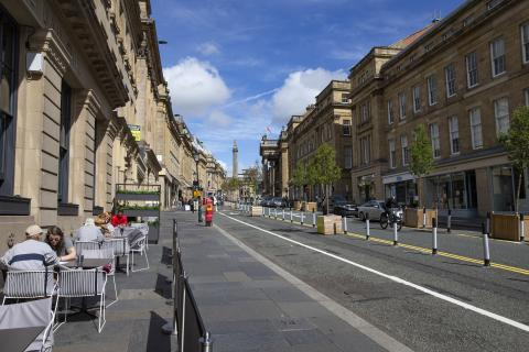 Photo showing Grey Street in Newcastle. There are people sitting at a pavement cafe on the left and part of the road has been sectioned off with temporary bollards to create extra walking space and a cycle lane.