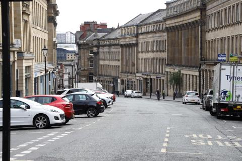 Photo shows the view down Grey Street in Newcastle with cars and a van parked on either side.