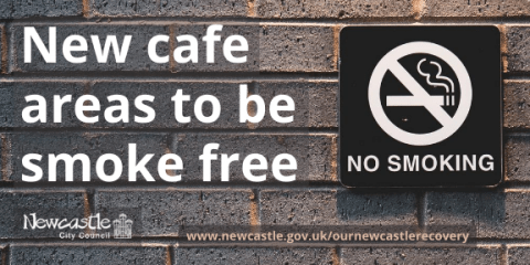 A black and white no smoking sign on a grey brick wall with the text New cafe areas to be smoke free