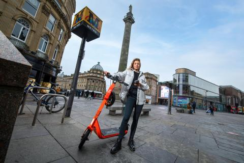 A woman is standing with an orange e-scooter in the centre of Newcastle next to a Metro station and with Grey's Monument in the background.