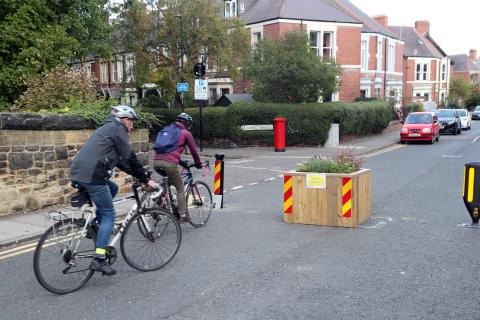 Two people on bikes ride along a street, with houses on the left,  that has been closed to vehicles using bollards and wooden planters.