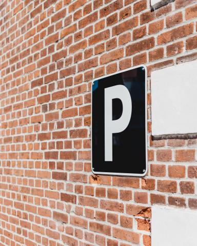 Photo showing a brick wall with a square parking sign with a white letter P on a dark background .