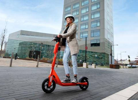 Photos shows a young woman riding an orange e-scooter with a tall building in the background.