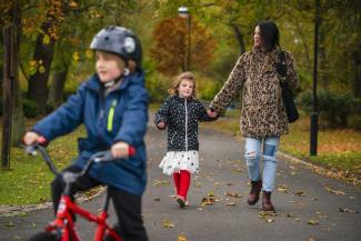 image of child cycling with mother and sister in the background