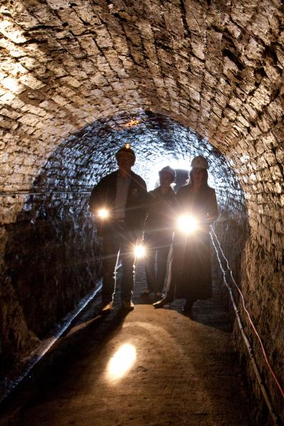 Three people in a tunnel wearing safety hats and carrying electric torches.